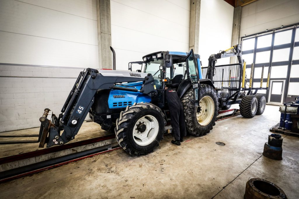 Valtra traktori ja tukkikärry traktorihuollossa Konneservicen huoltohallissa